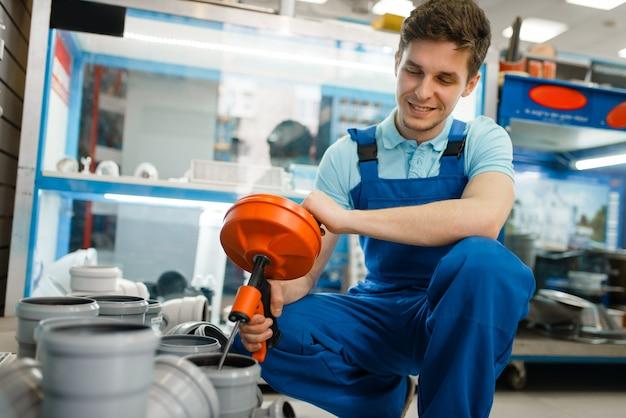 配管店のショーケースで制服を着た衛生技術者。店で配管工を購入する配管工、下水道管とアダプターの選択