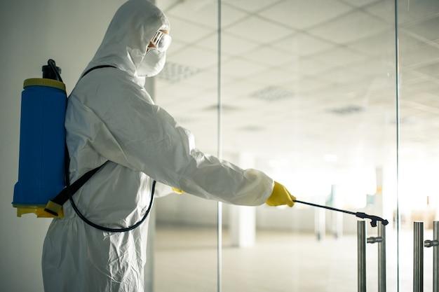 衛生労働者は、空のビジネスセンターに消毒液を噴霧して、covid-19の蔓延を防ぎます。ショッピングモールを掃除する消毒スーツを着た男性。誰も、健康、孤立した概念。