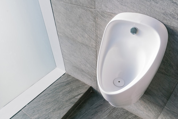 Sanitation white ceramic urinal in the men's bathroom with hygienic automatic water-saving electronic flusher.