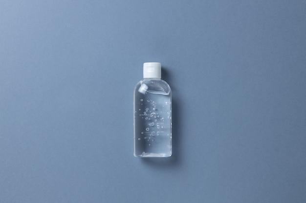 灰色の背景に、透明なボトルの消毒剤ゲル
