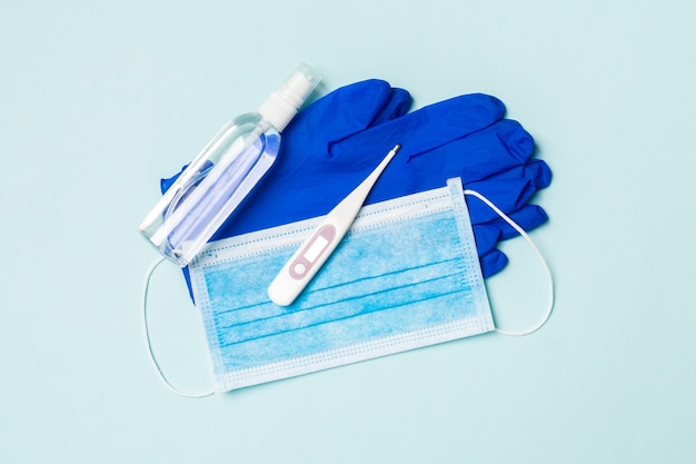 Дезинфицирующее средство, перчатки, цифровой термометр и медицинская маска