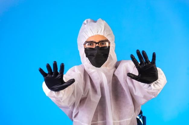 特別な予防のユニフォームと黒いマスクの消毒剤は一時停止の標識になります。