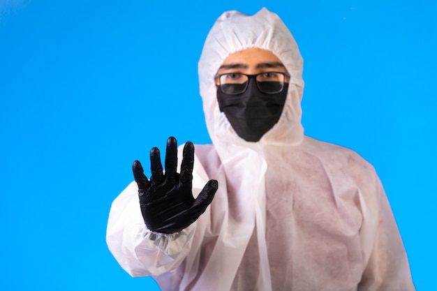 Sanitizer in special preventive uniform and masks on blue