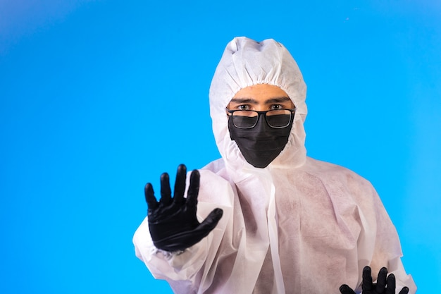 Sanitizer in special preventive uniform and masks stops the danger with one hand.