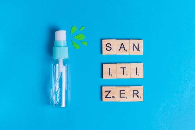 Sanitizer in spray on a blue background with green drops to protect health from bacteria and viruses