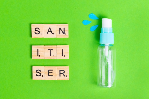 Sanitizer in spray on a green background with blue drops to protect health from bacteria and viruses