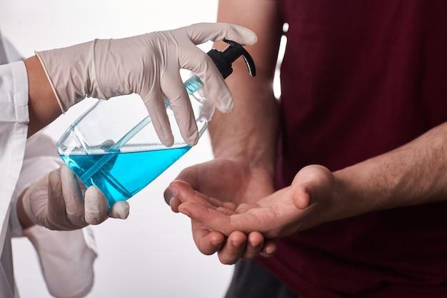 Коронавирус. доктор дает sanitizer гель в руки пациента. работа на дому, карантин. чистящий руки антибактериальный гель для устранения микробов. останься дома.