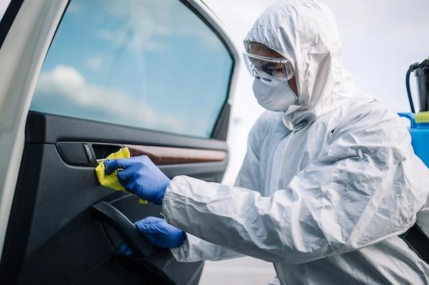 살균 서비스 작업자가 차량 내부를 노란색으로 청소합니다.