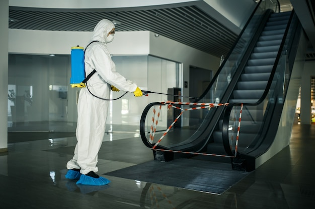 Sanitizing worker disinfects the escalator with a spray at the empty shopping mall to prevent the covid-19 spread in public places.