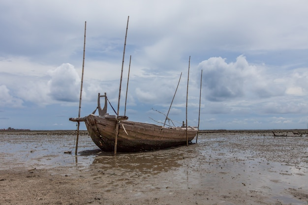 Sank fisherman boat on sand beach and mud