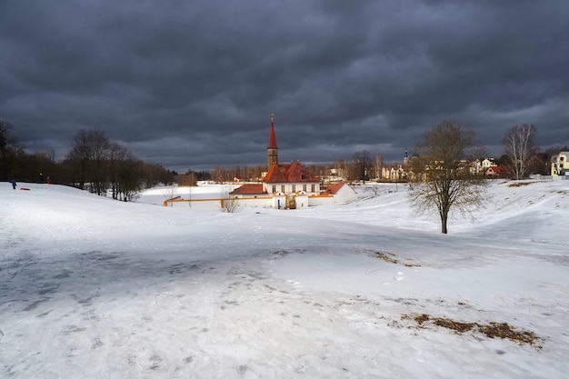 Sanny spring view of the old palace. white snowy landscape with old maltese palace in beautiful natural landscape. gatchina. russia.