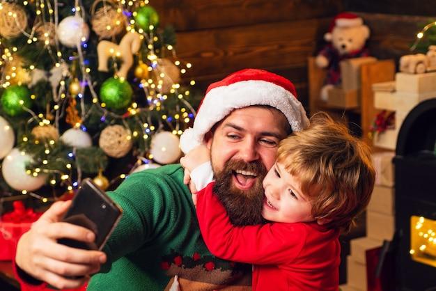 スマートフォンを使用してサンタと古いひげを生やしたサンタ。冬のクリスマスの感情。インターネット、ワイヤレス、