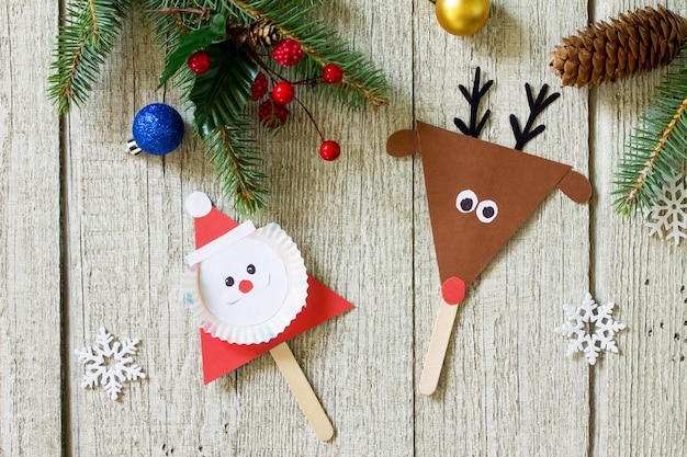 サンタとトナカイは木製のテーブルにギフトを貼り付けます子供のための手作りプロジェクトの工芸品