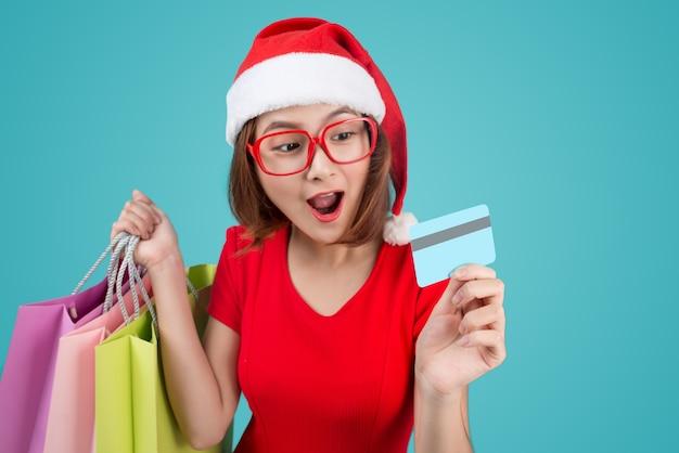 青いビネットに対して買い物袋とクレジットカードを保持しているサンタアジアの女性