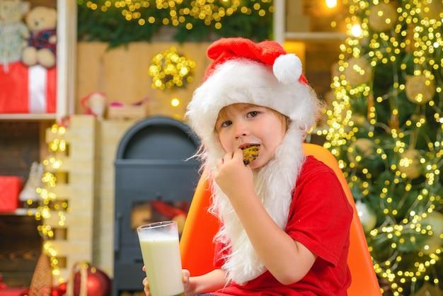 クッキーを食べて牛乳を飲むサンタの男の子の子供。サンタの帽子をかぶったサンタの男の子