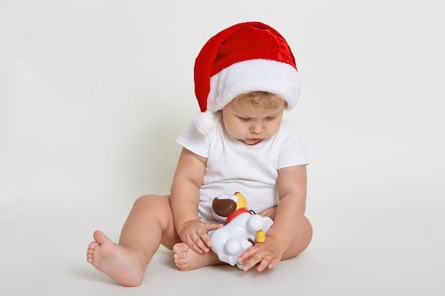 Мальчик санта играет с игрушкой тумана, изолированной над белой стеной, босиком младенец в боди смотрит на игрушку, младенец смотрит вниз, милый ребенок в канун рождества.
