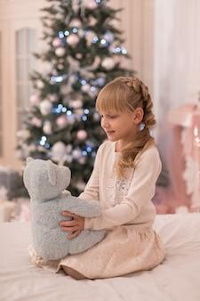 산타는 크리스마스에 어린 소녀에게 테디 베어를 가져 왔습니다.