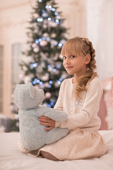 Santa brought a teddy bear to the little girl for christmas.