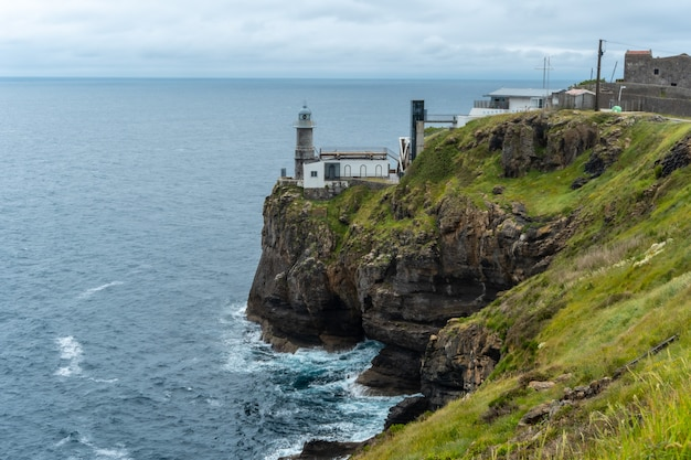 Santa catalina de lekeitio lighthouse and its beautiful cliffs on a cloudy spring morning, with the sea in the background, landscapes of bizkaia