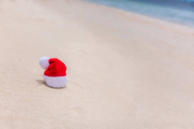 Santa christmas hat in sand on a tropical beach. holiday tropic summer