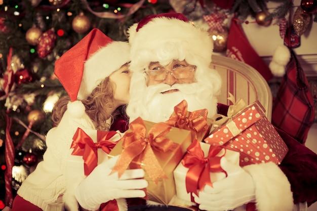 サンタクロースと子供が家にいます。クリスマスプレゼント。家族の休日の概念