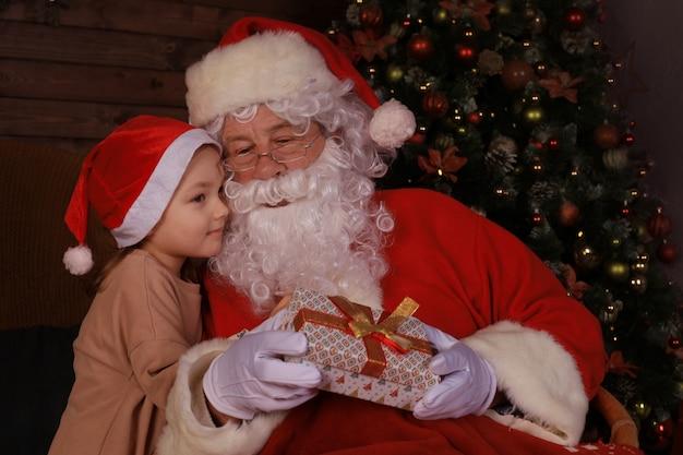 산타 클로스와 집에 있는 아이. 크리스마스 선물. 가족 휴가 개념입니다.