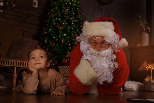 산타 클로스와 집에서 바닥에 누워 아이. 크리스마스 선물. 가족 휴가 개념입니다.
