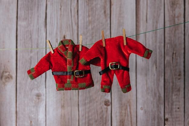 サンタクロースとクリスマスエルフの服は洗濯バサミで吊るされていました。スペースをコピーします。セレクティブフォーカス。