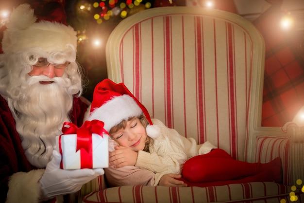 산타 클로스와 행복 한 아이입니다. 아이들은 꿈을 꿉니다. 크리스마스 휴일 개념입니다. 크리스마스 선물