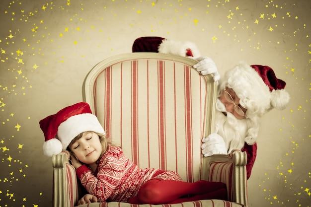 산타 클로스와 잠자는 아이. 아이들은 꿈을 꿉니다. 크리스마스 휴일 개념입니다. 크리스마스 기적
