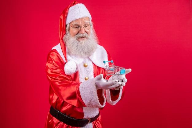 Дед мороз и супермаркет, он показывает мини-тележку. рождество и концепция покупок.
