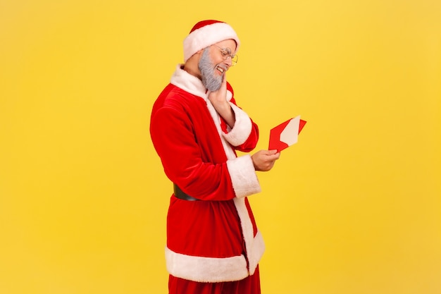 Santa claus being touched with sensitive letter, reading christmas congratulations.