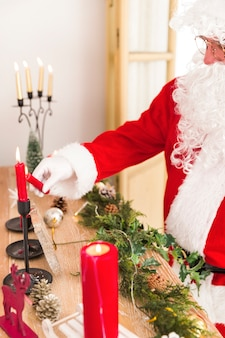 Santa claus brightening new year candles