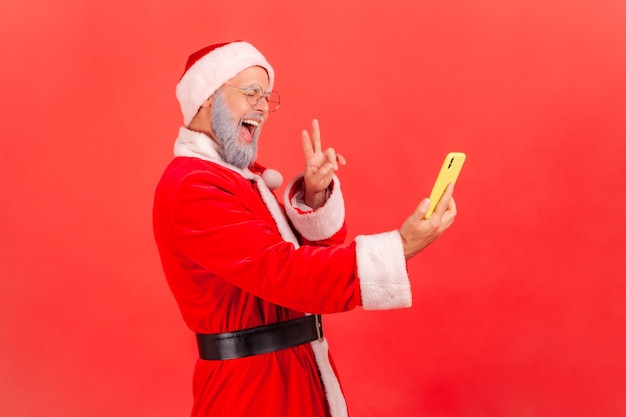 Santa claus broadcasting live stream, showing v sign to followers, excited expression.
