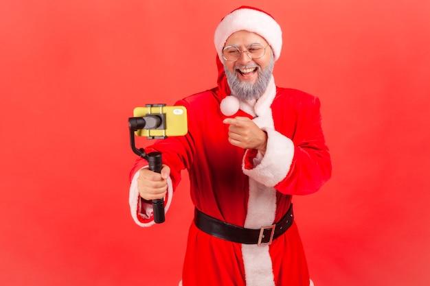 サンタクロースがライブストリームを放送し、電話とステディカムを使用して、デバイスのディスプレイに指を向けます。