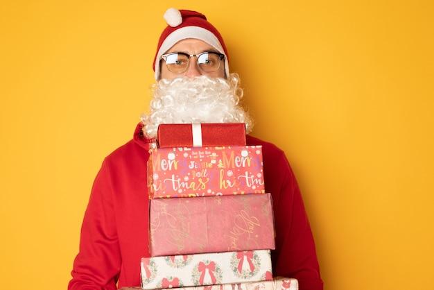 산타클로스가 크리스마스 선물을 가져왔습니다. 노란색 배경에 현대 젊은 산타