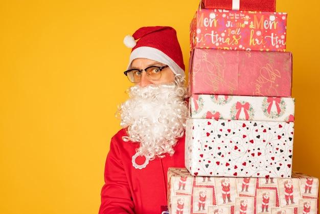 サンタクロースはクリスマスのプレゼントを持ってきました。黄色の背景に現代の若いサンタ