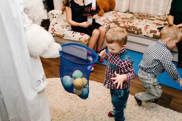 サンタクロースは子供たちに贈り物を持ってきました。贈り物で遊ぶ楽しい子供たち。新年のコンセプト。メリークリスマス。休日、クリスマスの家族、子供時代と人々の概念。