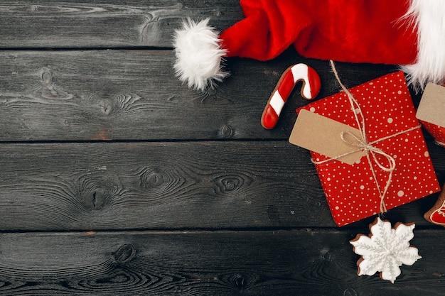 Шапка санта-клауса и рождественский подарок на деревянном фоне вид сверху