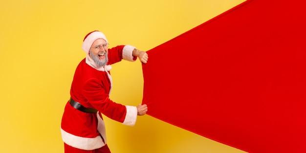 선물이 든 큰 가방을 들고 있는 산타클로스, 광고를 위한 복사 공간.