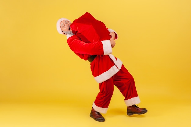 Santa claus carrying big heavy bag with christmas presents, congratulating with new year.