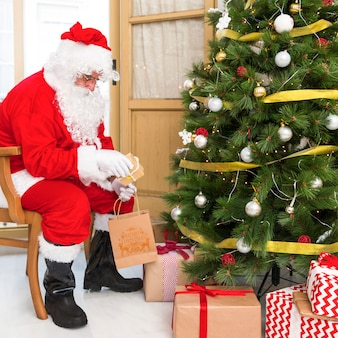 Santa claus on chair putting gifts under tree