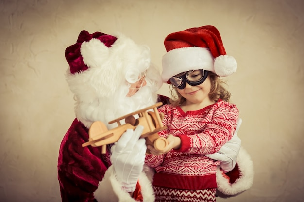 Santa claus and child playing with vintage wooden plane at home christmas gift holiday concept