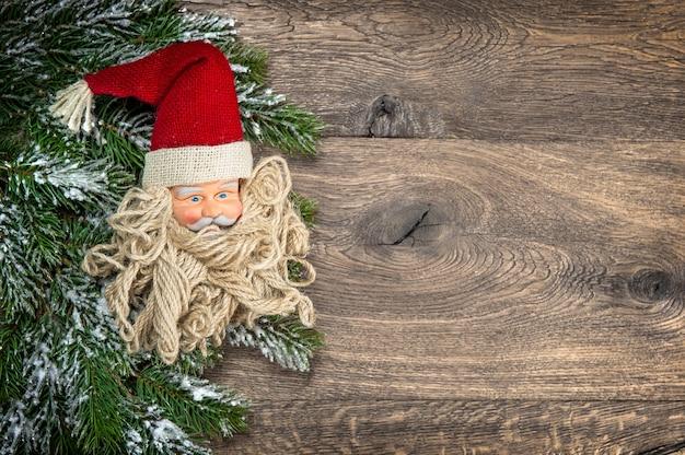 木製の背景に松の木の枝とサンタクロースのクリスマスの装飾。ビネット付きのビンテージスタイルのトーンの写真