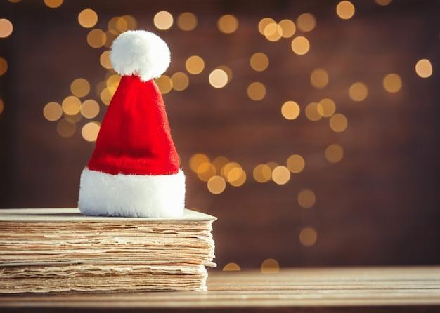 Santa claus christmas hat and old books Premium Photo