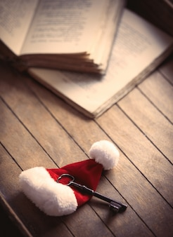 Santa claus christmas hat with classic key and old books