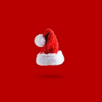 Santa claus christmas red hat is flying in the air on a red background. sale. levitation concept. christmas layout with copy space.