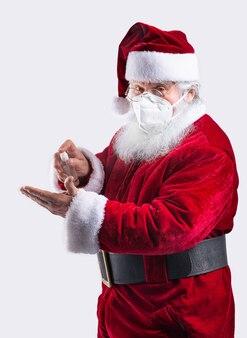 サンタクロースがジェルで手を掃除し、マスクを着用して白い壁にコビッドを防ぎます