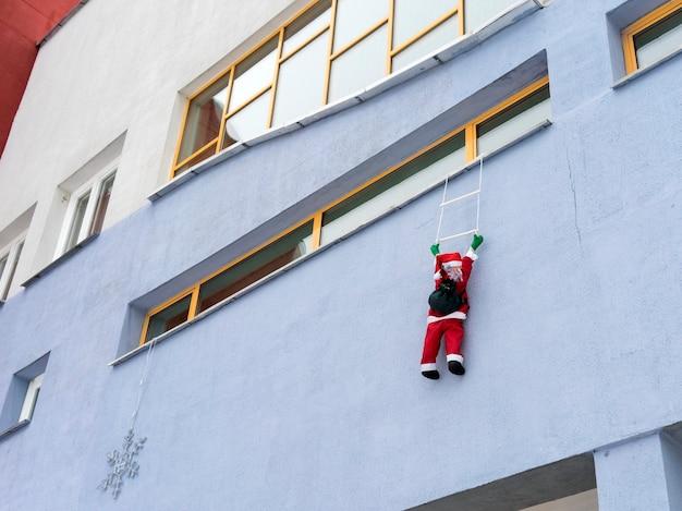 Дед мороз поднимается на стену с подарками