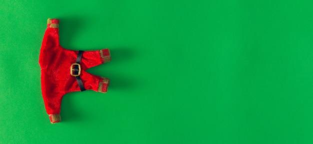 緑の背景にサンタクロースの服。クリスマスの飾り。スペースをコピーします。セレクティブフォーカス。